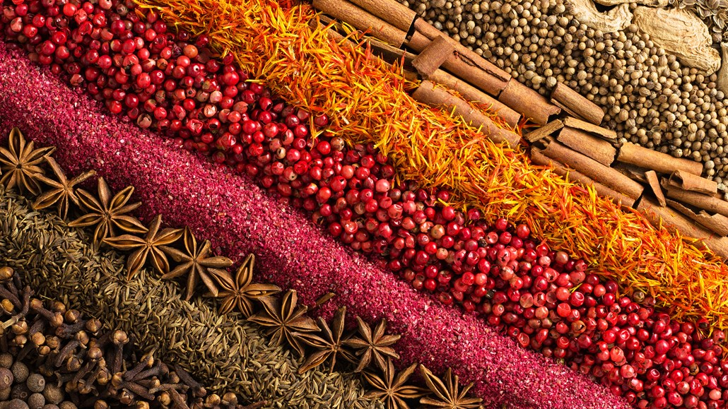 Rows of spices, such as allspice, clove, cumin, star anise, red peppercorns, saffron, cinnamon, coriander