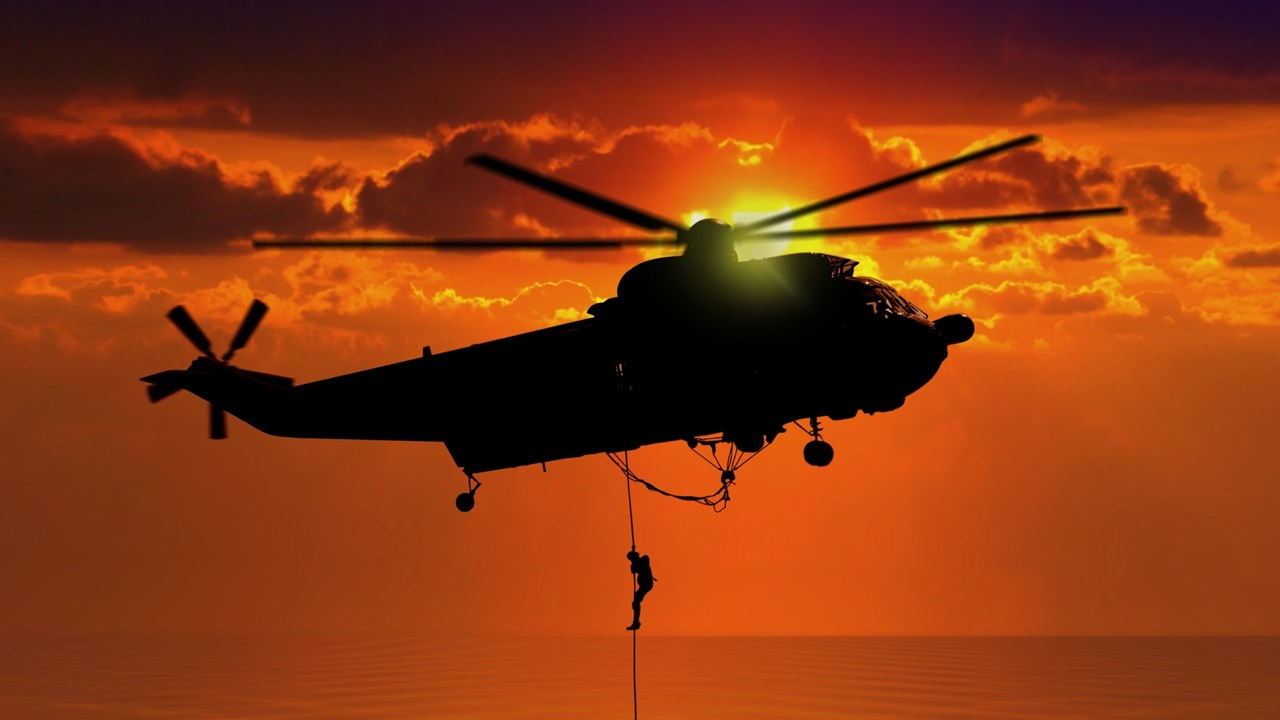 helicopter flying through sky with man hanging off rope